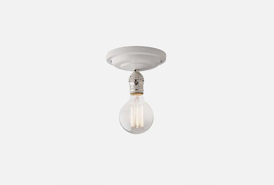 The Defiance Surface-Mount Fixture from Schoolhouse Electric is available with a white or black porcelain canopy cover and a black or nickel socket finish; $109.
