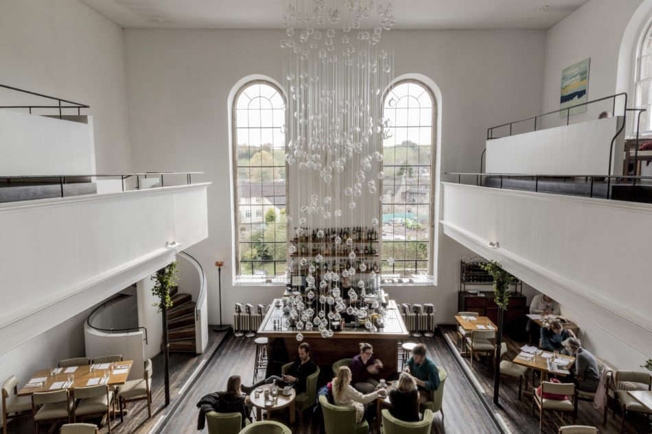 The double-height dining room is illuminated by a cascading glass fiber optic chandelier by Bruce Monro. The owners enlisted architects Mackenzie Wheeler to oversee the rehabilitation of the building. Photograph courtesy of The Modern House.