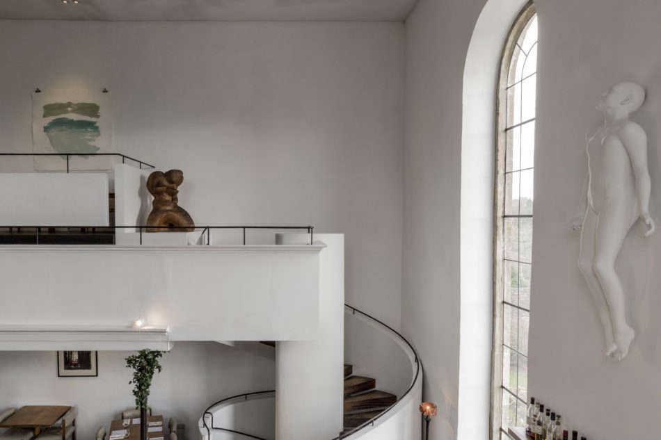 """In the interior, """"materials are limited to reclaimed oak, local Doulton stone, simple blackened wrought iron fittings,"""" the architects say. Faith by Lucy Glendinning is on the wall to the right. Photograph courtesy of The Modern House."""