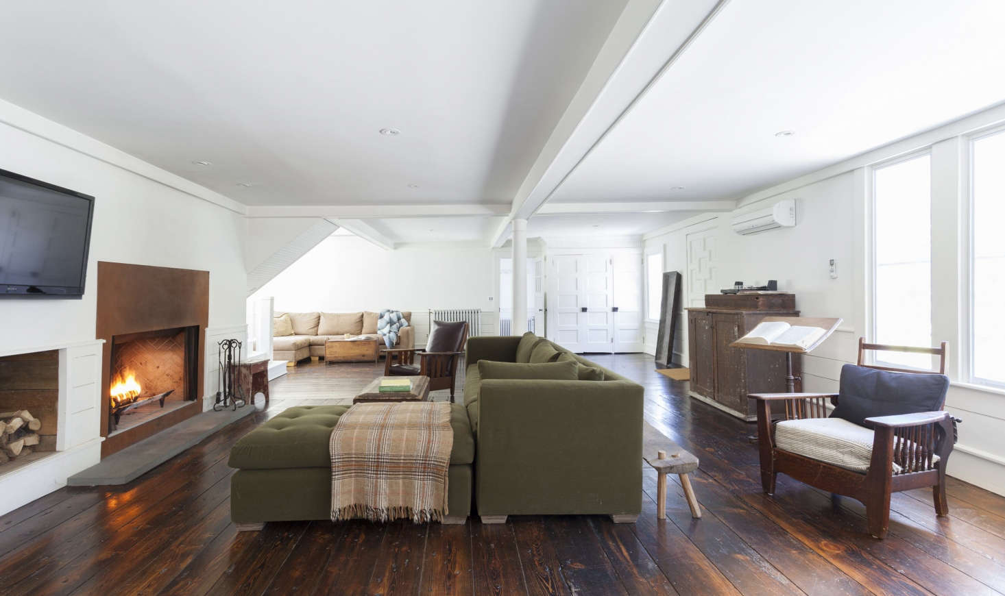 "The open-plan living room/family room/dining room has its own steel-front fireplace and original wide-plank floors. The wainscoting and ceiling coffers were built from pine trees felled and milled on the property. The living room is painted in Benjamin Moore's Decorator's White. ""My trifecta is White Dove, Decorator's White, and Super White,"" says Givone about his favorite Benjamin Moore paints."
