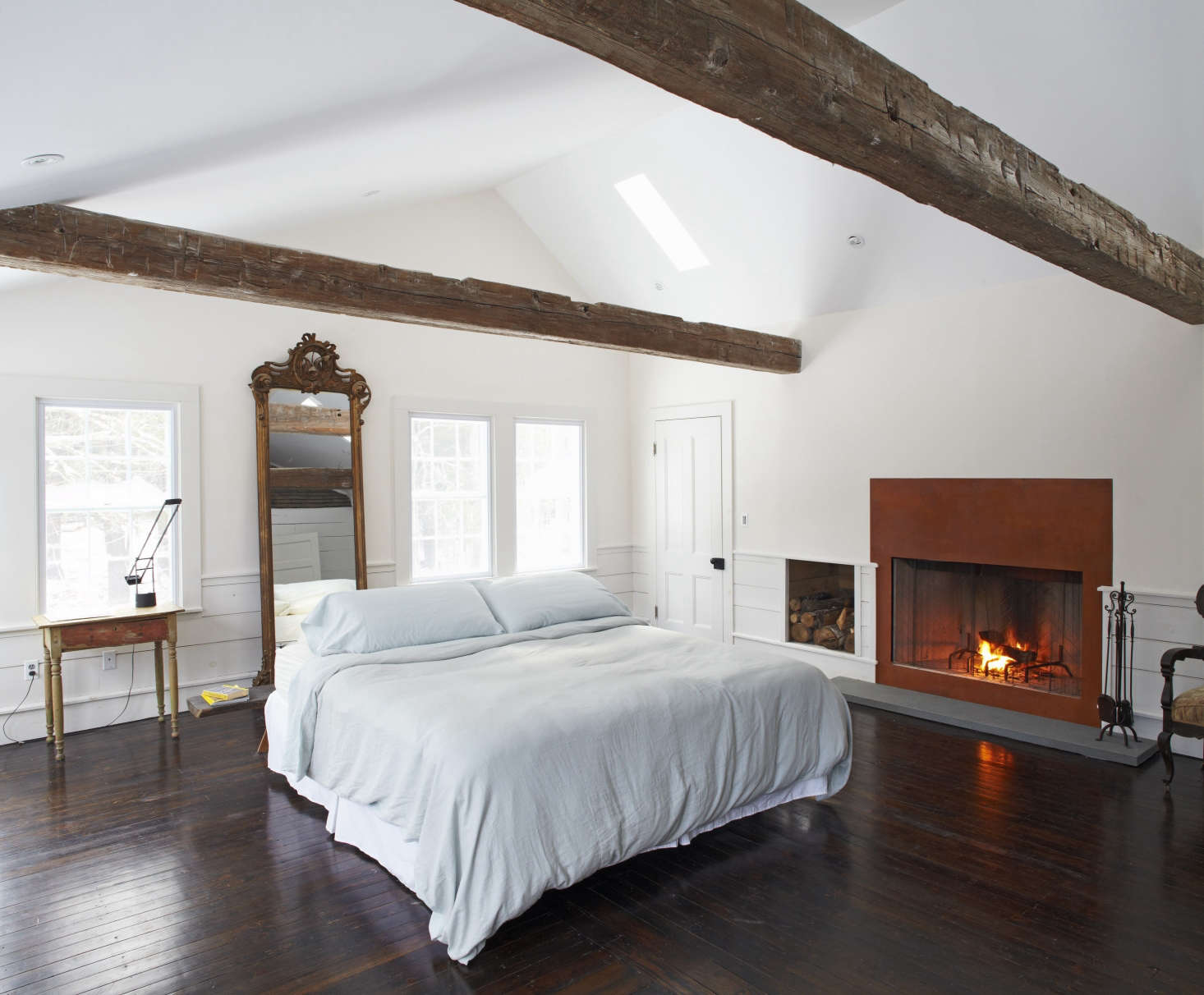 In the master suite–one of five bedrooms–the bed is floated in front of an antique mirror and alongside a wood-burning fireplace.