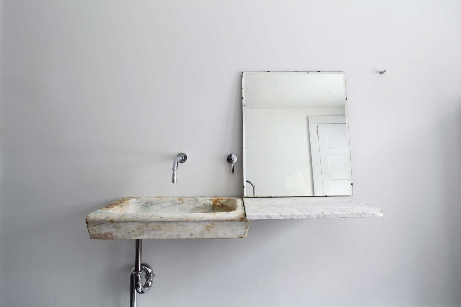 An 18th-century Italian marble sink seems to hover, thanks to angled supports concealed in the wall. The house has 2.5 baths.