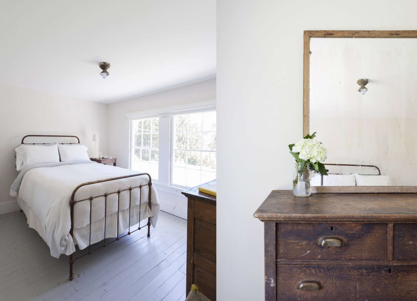 An old cast-iron bed frame and a minimalist layout in a farmhouse bedroom. The windows have their original wavy glass.