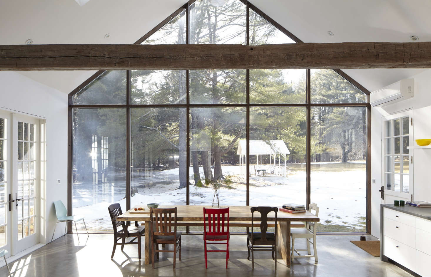 The kitchen resides in a modern addition that echoes the roofline of the original house. The 22-foot-high glazed curtain wall is skyscraper glass in a steel framework; it overlooks a brook and a gazebo.