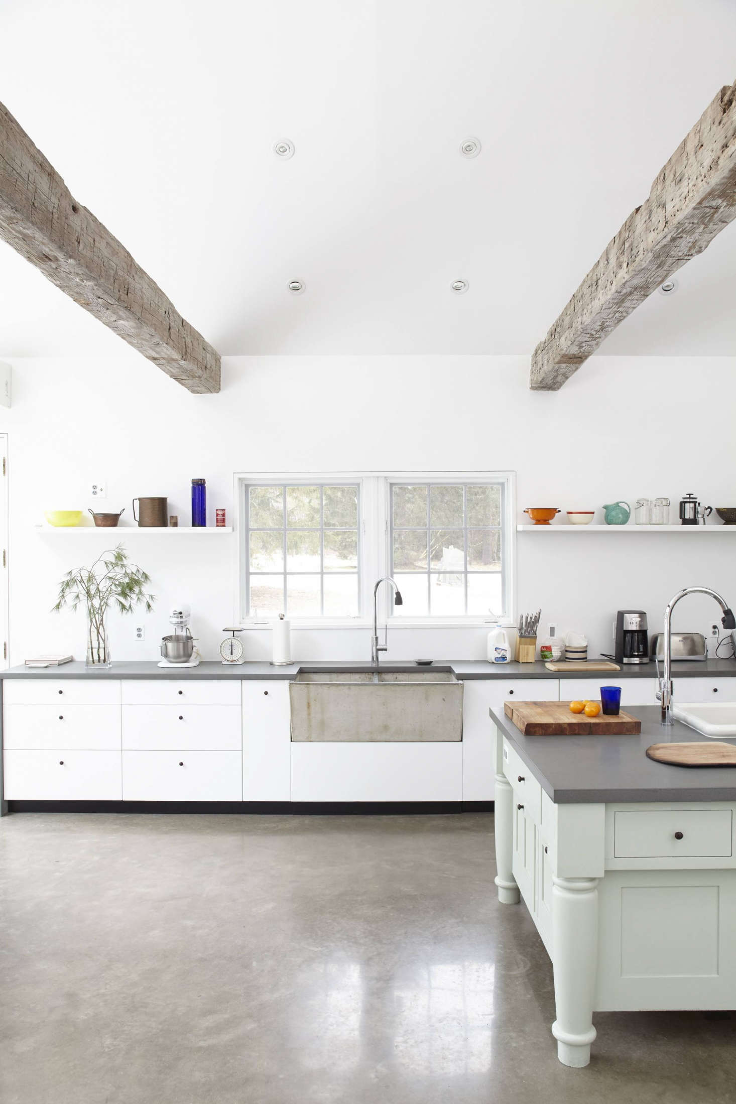 Bluestone countertops and lacquered cabinetry contrast with a vintage concrete sink. The floor is polished concrete.