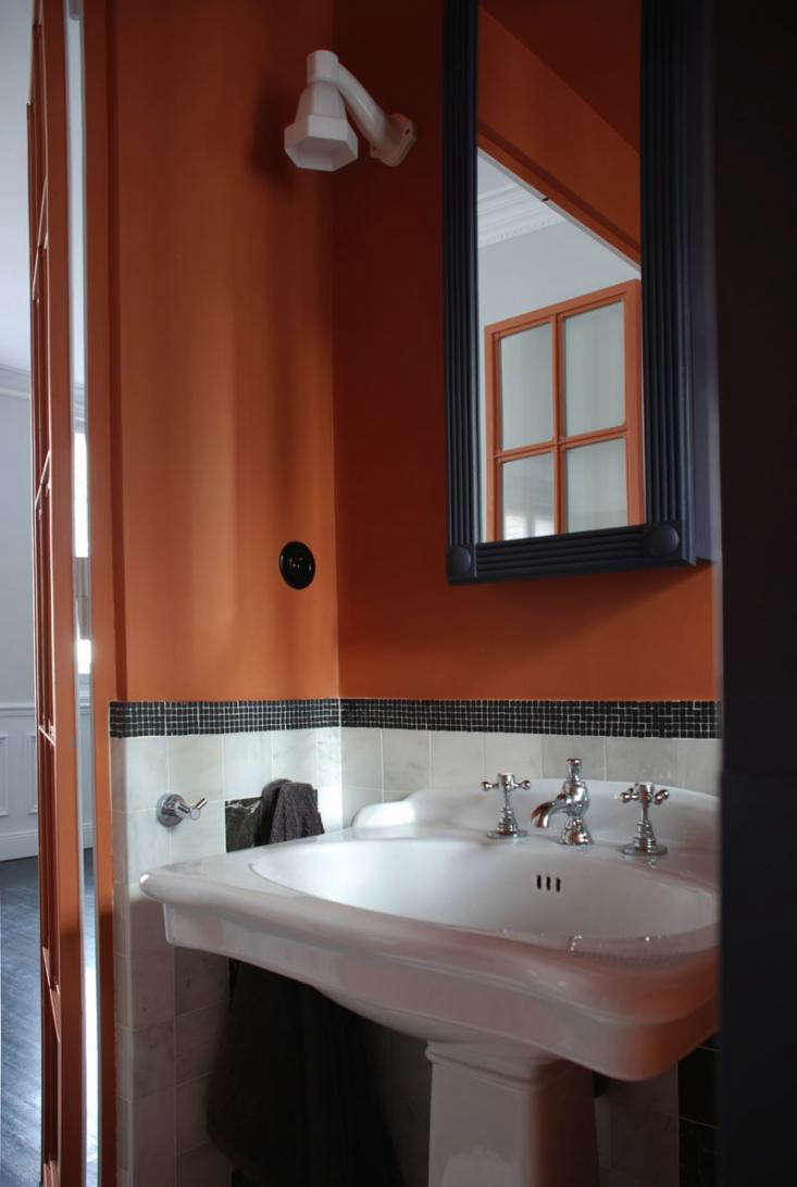 pair that orange with green marble tile and traditional fixtures and fittings to recreate the look see our sources below to see the rest of the house
