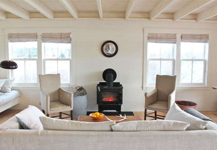 At Harbor Cottage in Maine, all the furniture, even the woodstove, has been downsized to fit the small living area. Photograph by Justine Hand from A Cottage Reborn in Coastal Maine.