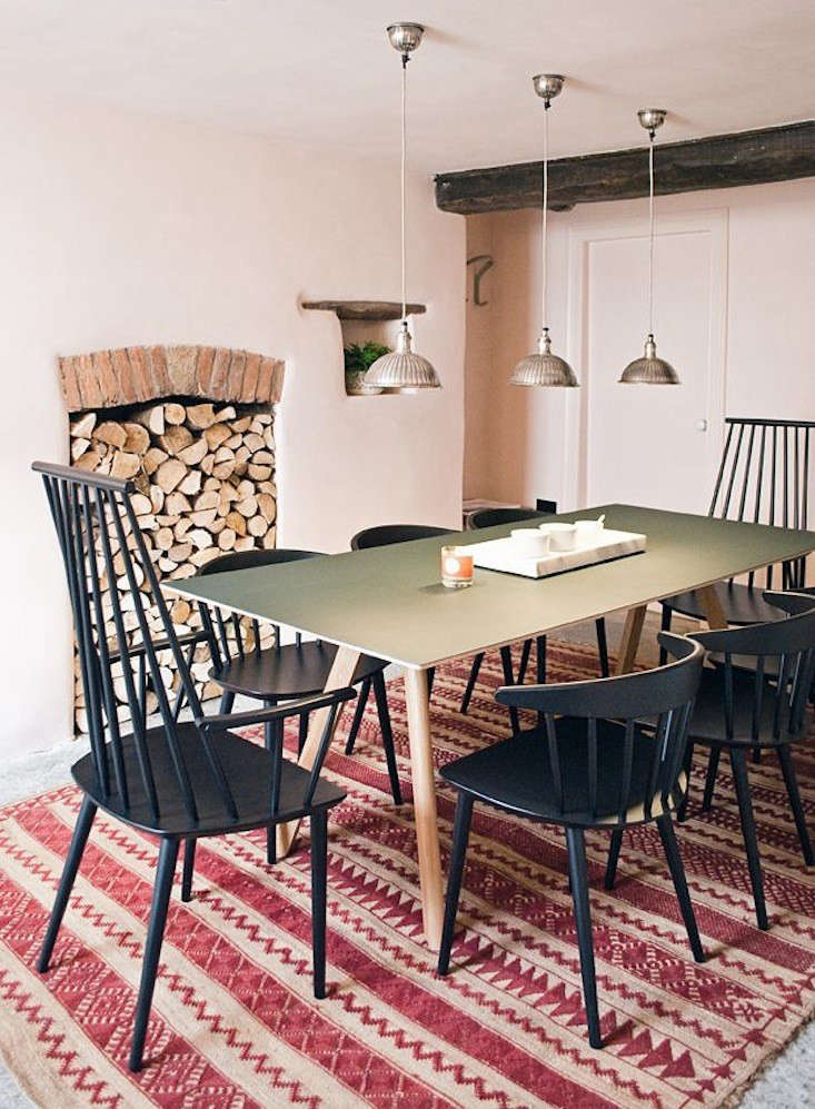 ACopenhague Table (plywood with green linoleum top) is paired withJ110 Chairs and J77Chairs (black lacquered beech), all by Hay.The lamps are from Rockett St George. Photograph by Abi Dare.