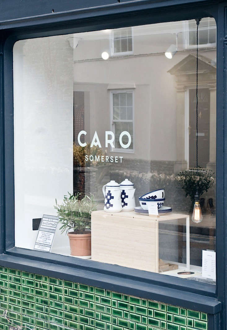 """A peek into the shop from a tile-clad window with enamelware by Welsh brand Blodwen on display. Caro occupies three ground-floor rooms in an 18th-century stone building, and the Victorian green tiles, Jones tells us, were revealed under a layer of cream paint. """"All it took was a bit of scrubbing."""" Photograph by Abi Dare."""