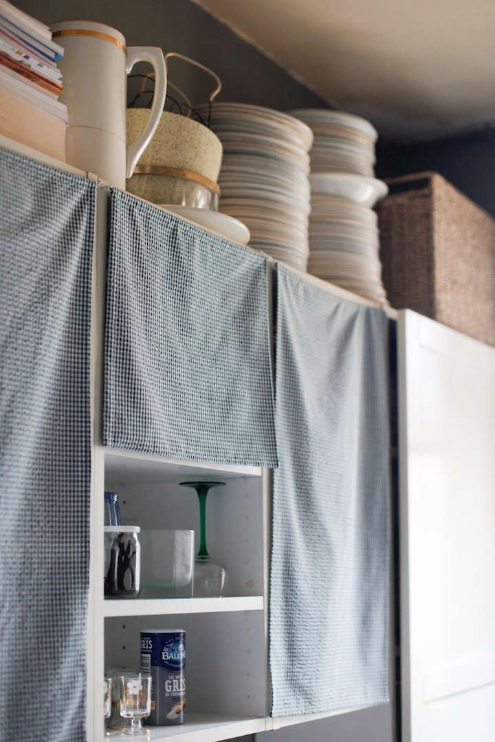 "If you're not ready to go for the completely open look, tack pretty lengths of cloth in place of cabinet doors. In Done/Undone with Clarisse Demory in Paris, Demory removed her Ikea cabinet fronts and hung blue tea towels instead. ""It's less cold, less artificial this way,"" she says."