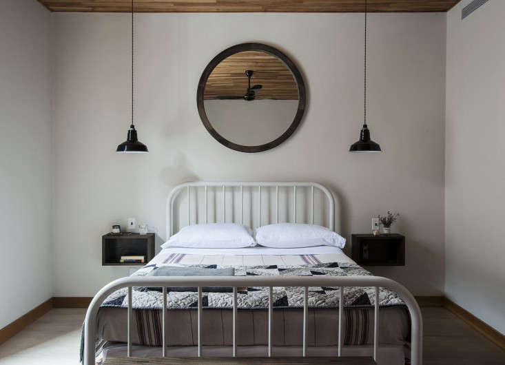 """InA Cobble Hill Transformation,architect Oliver Freundlich used pendant lights for bedside illumination. """"The idea was to keep the bedroom spare and the furnishings low, and allow the wood ceiling to soar,"""" says Freundlich. """"The pendants dropping from the ceiling add some drama to the height."""" (There are dimmer switches next to each side for easy on and off.) The lights are Barn Light Electric'sIvanhoe Dino Porcelain Cord Pendant Light.Photograph byMatthew Williams."""
