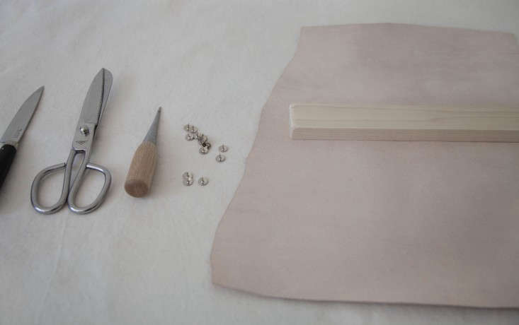 Step 1: Flip the leather over so that the inside of the hide faces up. Sand your pieces of wood, place atop the leather, and eyeball how you'll wrap it. Measure, mark a pattern, and then cut to your liking.