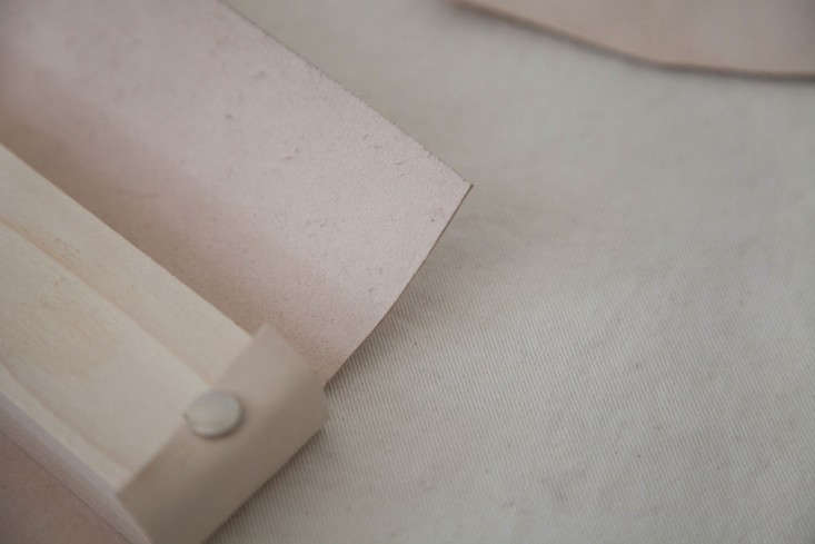 Step 2: On each end of the wooden block, trim the leather so that it can be wrapped tightly against the wood.