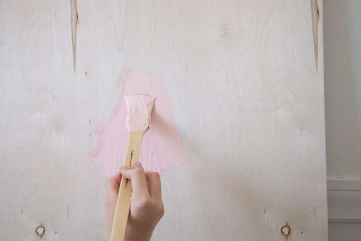Step 1: Stand your panel of wood up against a wall on top of a painter's drop cloth to catch any drips. Begin painting your board by brush or roller (your choice).