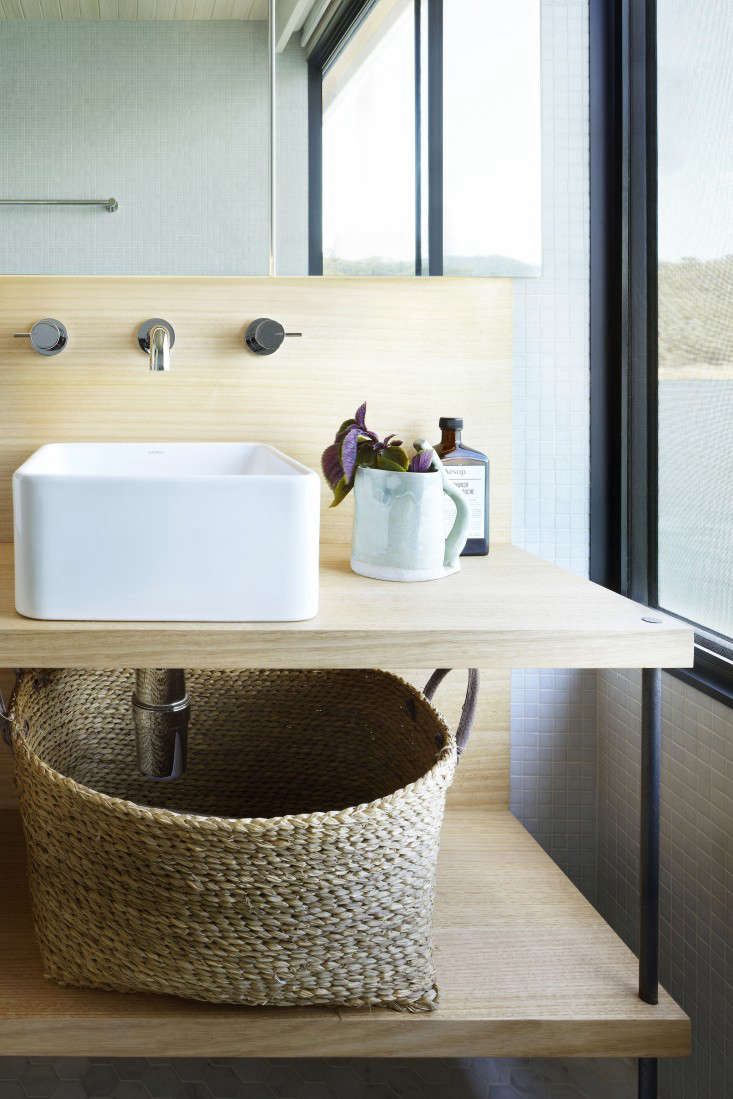 Luxury Above The bathroom vanities are solid Australian stringybark a eucalyptus with blackened steel legs The cube basin is from Australian bath pany
