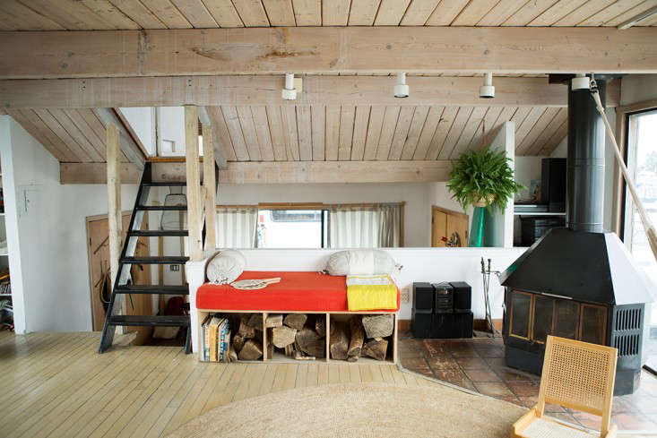 A built-in daybed (with firewood storage) and a woodstove in the living room.