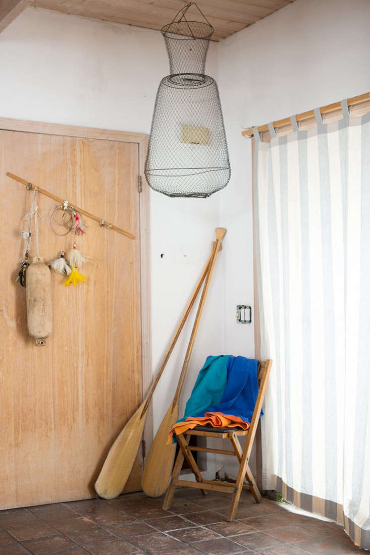 A curtained sliding glass door leads to the entry hung with a fishing trap. That&#8