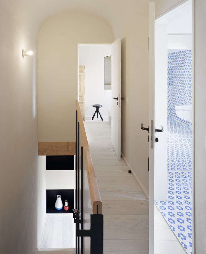 The bathroom's honeycomb floor tiles extend up the walls.