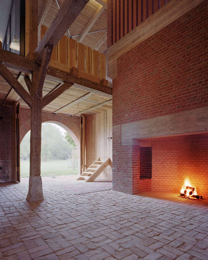 "Kröger describes his design as applying ""the preexisting language of the house and adapting it using its own means and rules."" The house is centered by a double-height great hall with a fireplace (a necessity because the room is unheated). Note the inset sitting niches in the hearth."
