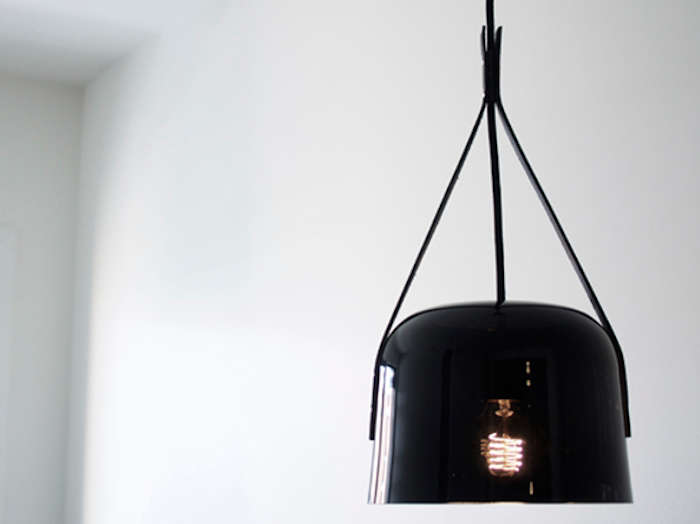 Above: The black glass pendant diffuses light to create a dim atmosphere in  the room.