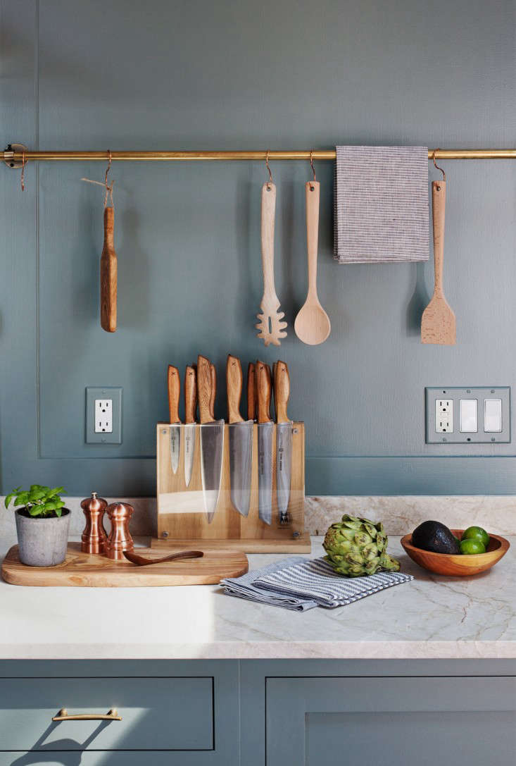 Wooden utensils are given a place of honor on a brass rail that runs the full length of the kitchen in a family's weekend home on the North Fork of Long Island. Photograph by Heidi's Bridge from Building Character: Jersey Ice Cream Co. and the Case of the Charmless Manse.