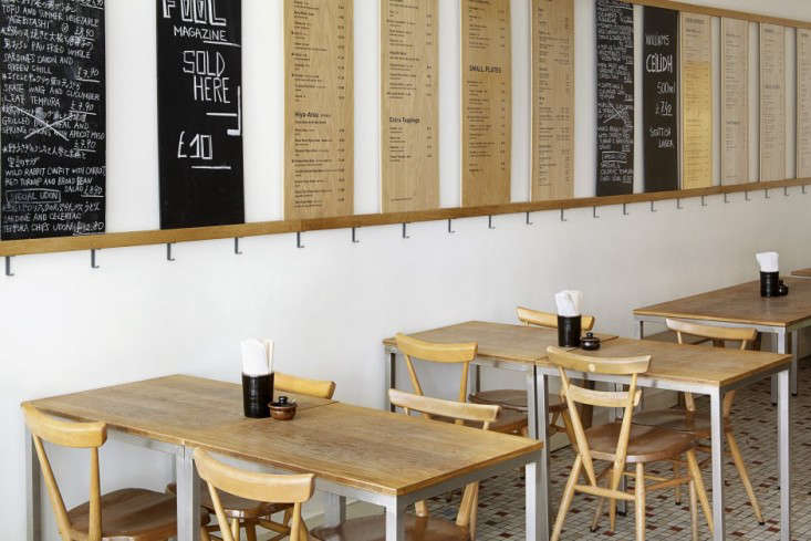 above designer michael marriot lined the walls with menus that alternate between oak and blackboard surfaces the tables are surrounded by ercol stacking