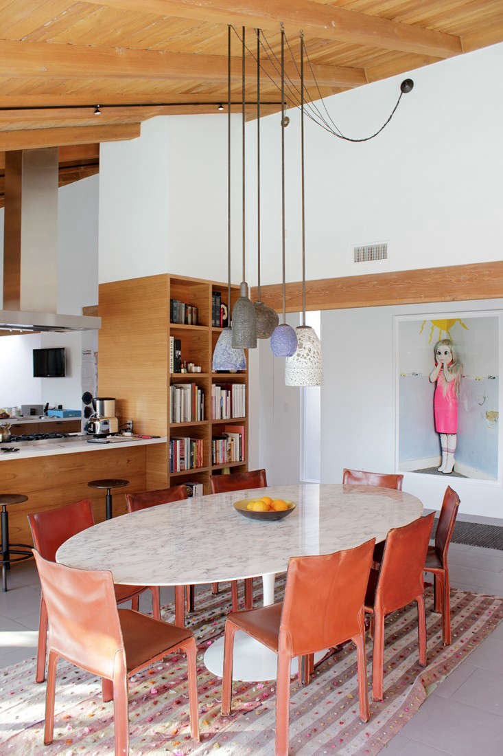 The table stands next to the U-shaped kitchen, which architect Julie Hart opened up to the dining room. After taking down the wall, she added built-in bookshelves that conceal the refrigerator on the other side. The photograph is by artist Laurie Simmons, a friend of Carla&#8
