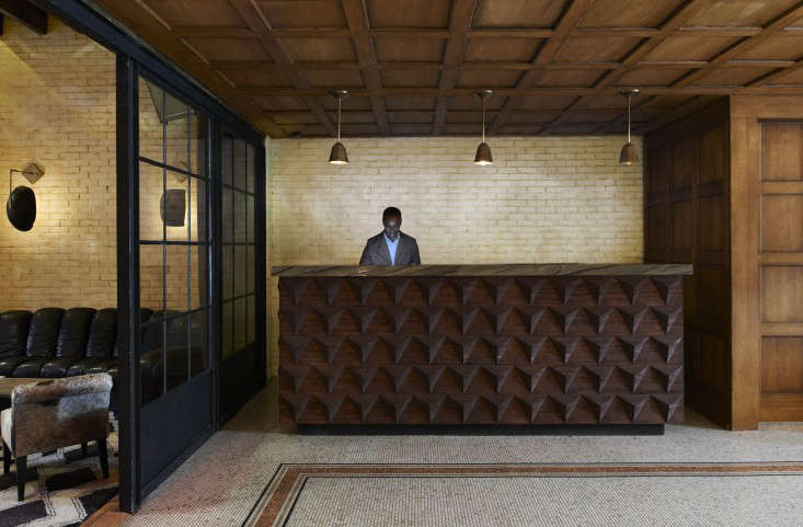 above in the lobby parged brick wallsbrick thats been skimmed with a layer of cement to soften the surfaceset off classic wood paneling and a graphic
