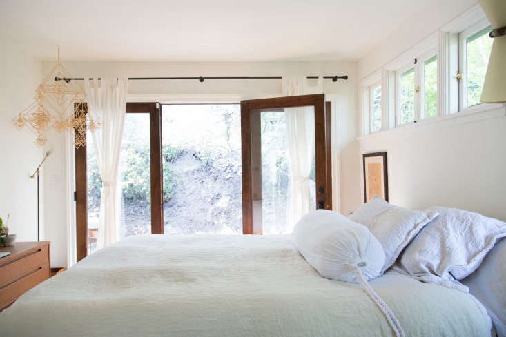 In their remodeled Pasadena bungalow, fashion designers Momo Suzuki and Alexander Yamaguchi replaced single doors and windows with French doors, like these in the airy bedroom, to connect indoors and out. A tip: for affordability, the couple opted for wood-framed windows from Home Depot at $0 a panel and stained the wood themselves; a friend made the handles. See more in Midcentury Meets Zen: A DIY Remodel in LA.