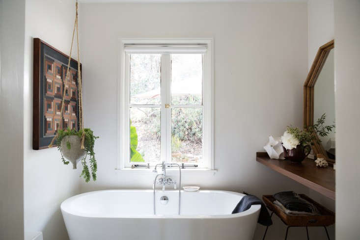"""A window removed from the guest room was put to use in the overhauled bathroom. The couple found a bathtub they liked in a showroom and then tracked down the same model online for less. """"We wanted to have a view from the tub, so we moved the bath to the window wall."""" They had the mirror fabricated by a local frame shop and then finished it to match their walnut counter. Adds Momo, """"Because the space is small, we wanted it to feel more like a room than a bathroom, so we added tileonly to the shower area—we bought discontinued subway tile for 99 cents a square foot."""""""