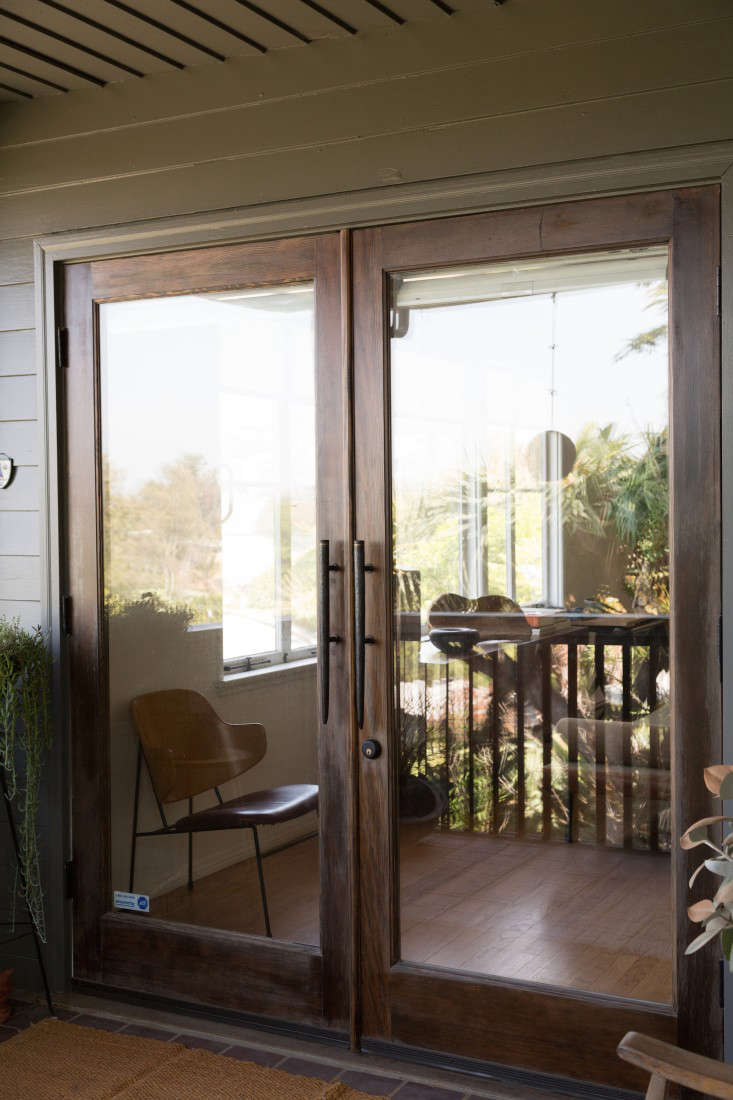 To connect indoors and out, Momo and Alexander installed several sets of French doors, including at the entry, shown here (where they replaced a single wood door). After puzzling over how to afford French doors, they used wood-framed windows, $200 a panel, from Home Depot and stained the wood themselves. A friend at Hot Metal Soup in New York made the front handles.