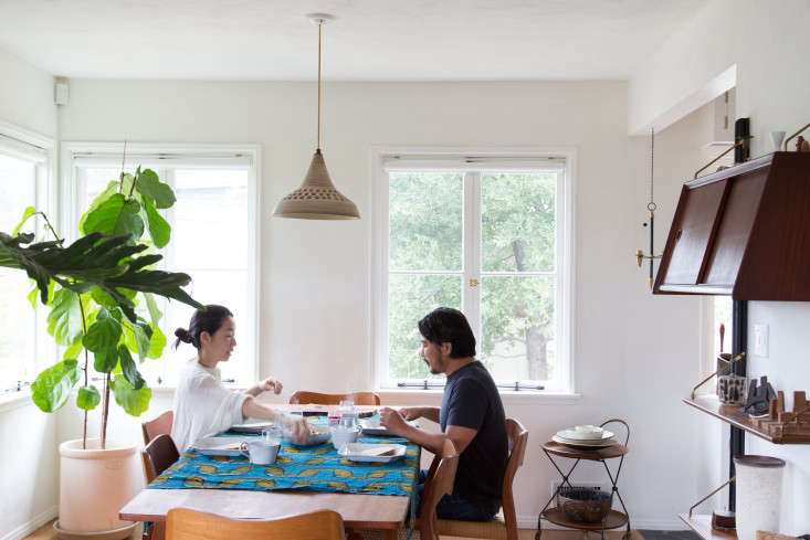 """""""We like to have long, leisurely breakfasts, enjoying the views of the big oak trees around the house,"""" says Momo. Here they're shown at their eight-foot-long table—""""chosen to emphasize an open feeling""""—with chairs by Arne Hovmand-Olsen."""
