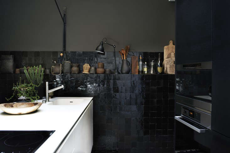 A black and white kitchen in Lyon, designed by Stephane Garotin and Pierre Emmanuel Martin of Maison Hand, has glossy black tiles and bitter chocolate walls; from Hilary Robertson&#8