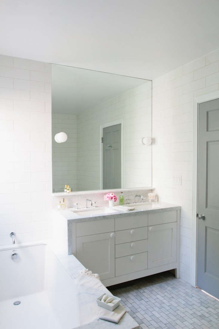 Marvelous Above Polished Carrara marble frames the bath and continues on the custom cabinet that us just big enough for a pair of sinks The door color is Benjamin