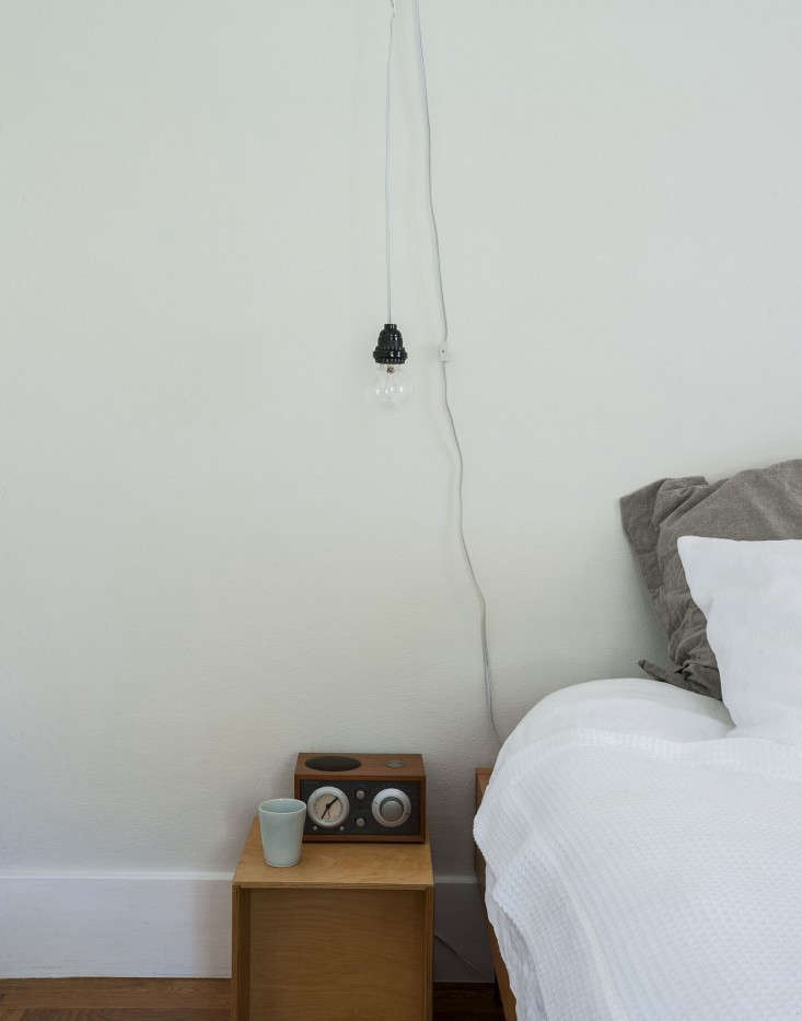 InSarah's Refined Rental in St. Helena,the master bedroom is small. Side table lamps would make it feel cramped, and drilling holes in the wall was not an option, so she sourcedsome hanging bulbs and used metal prongs intended for telephone wire to attach the lampcord to the ceiling.Photograph by Matthew Williams for Remodelista.