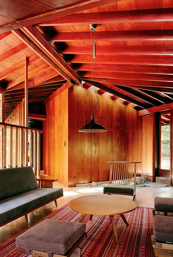 In the living room, the sofa, chair, and stools are by George Nakashima and are upholstered in Pierre Frey fabric. The rug is from Lost & Found in Los Angeles.
