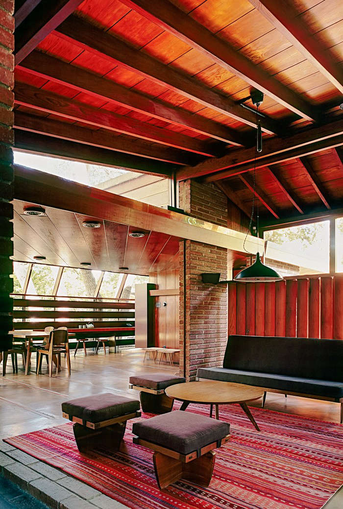 A view from the living room across the open space to the dining room highlights the multi-layered and richly textured materials of the wood, brick, and glass construction.