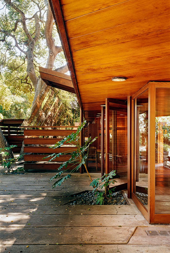 The indoor/outdoor qualities of Southern Californian living are enhanced by large pivot doors. Concrete floors run throughout the house and extend outside.