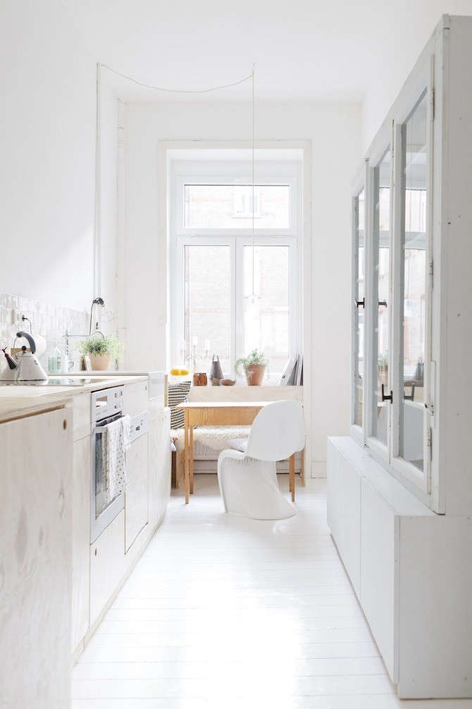 Plywood cabinets with cutout cabinet pulls in a bright German kitchen. (Note also the built-in plywood bench in the small breakfast area.) See Happiness at Home with a German Design Duo.