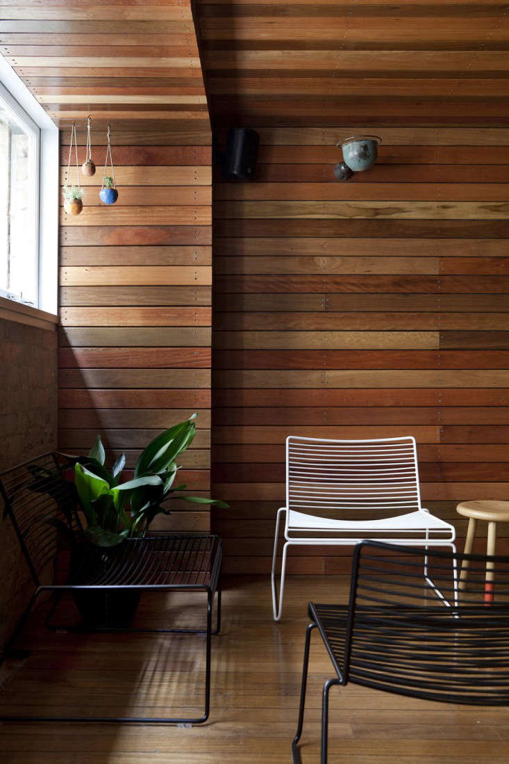 Above reclaimed wood panels outdoor furniture and potted plants lend an outdoor deck vibe to the mezzanine