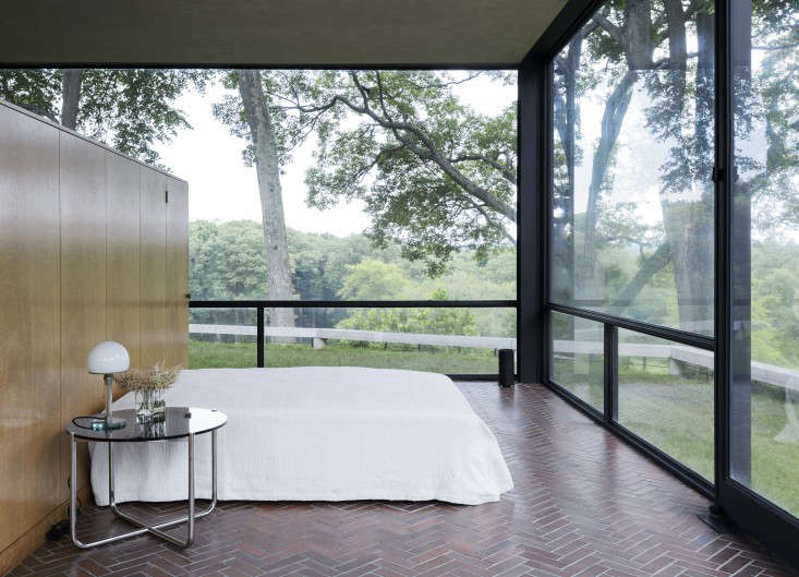 Above a 1927 mies van der rohe glass and tubular steel table stands next to a ghost of a bed cloaked in a woven cotton spread that johnson brought back