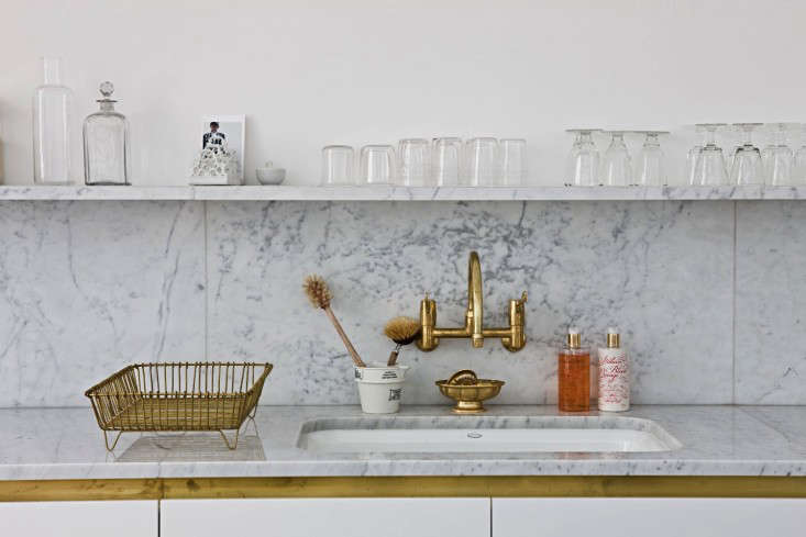 Unlacquered brass fixtures add warmth to the Carrara marble countertops, backsplash, and shelf.
