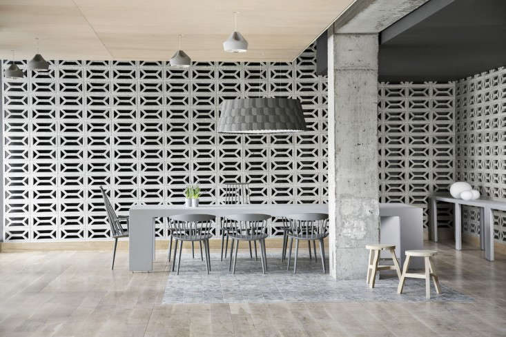 Cute Above A monochromatic conference table surrounded by J Chairs and J Chairs both in gray by Danish design studio Hay A pair of Tom Dixon Offcut