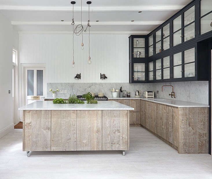The upper cabinets have a surprise lining of white subway tiles with dark grout. Clear glassware lines the shelves, allowing the design to shine through. Photograph courtesy of Blakes London.