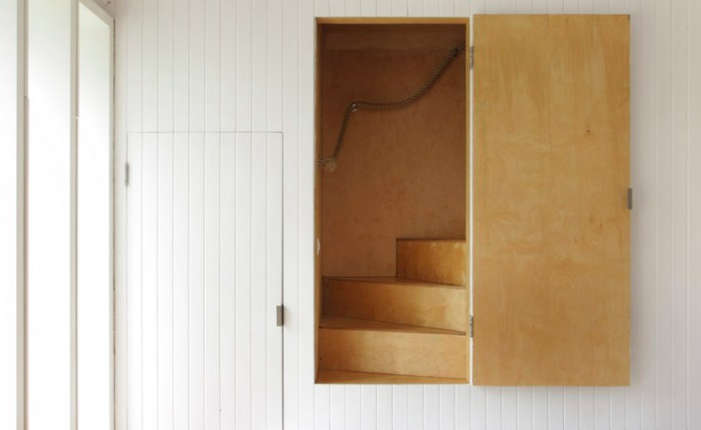 A concealed plywood staircase leads to a loft in The Brick Barn: A Modern English Farmhouse in Norfolk.