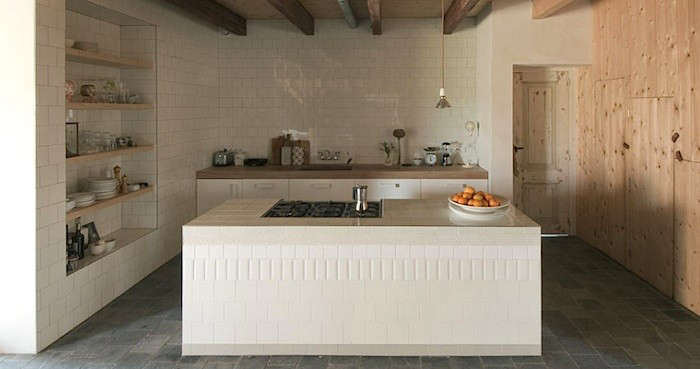 While most of the tiles are offset in this kitchen by Netherland designers Ina Matt, a stacked row of different-sized tiles creates a patternedband on the island. More of this project can be seen in Architect Visit: Studio Ina Matt.