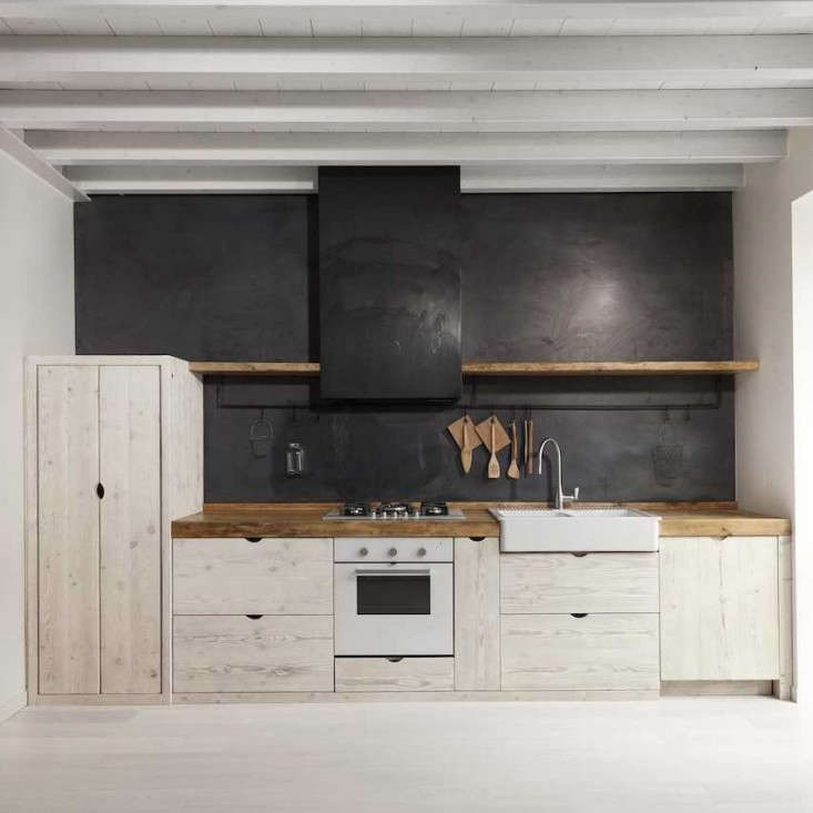 A minimalist iron utensil rail displays only a select few tools in a young restaurateur couple's Katrin Arens–designed kitchen. Photograph courtesy of Katrin Arens from Kitchen of the Week: The New Italian Country Kitchen by Katrin Arens, Scrap Wood Edition.