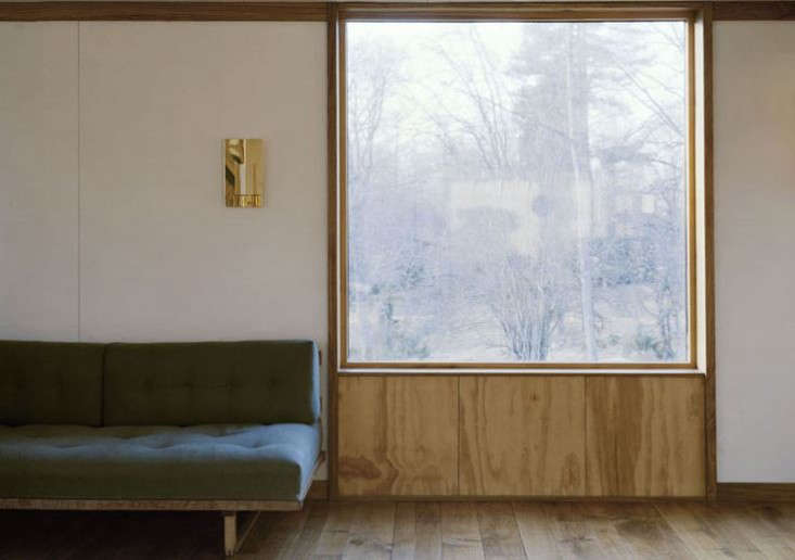 Plywood frames a window in a bare-bones summerhouse. SeeScandinavian Simplicity: A Reimagined Swedish Summerhouse.