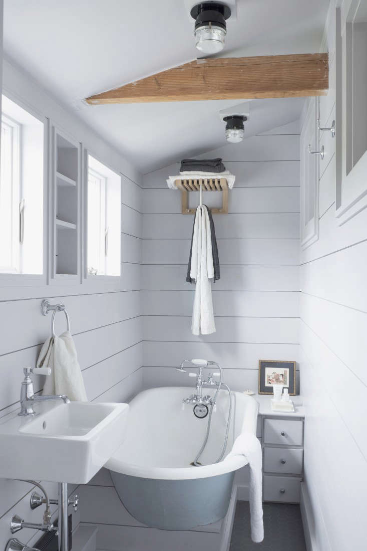 Great Above A shiplap paneled bath with a Mini Cutter Wardrobe by Skagerak for towels and Fresnel adjustable wall ceiling lights designed by Joe Colombo for