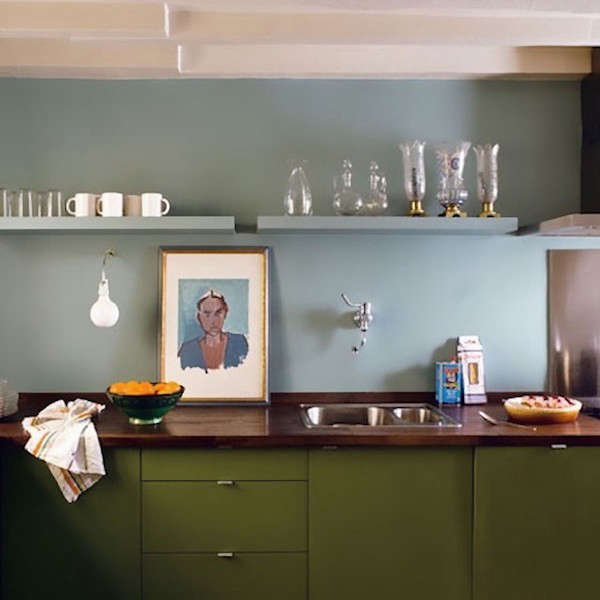 A kitchen in Paris by architect Philippe Harden, a portrait propped on the wood counter picks up the color scheme of pale blue and olive green.